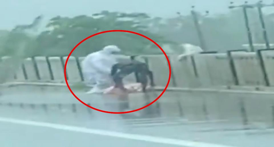 Two men are seen picking up the body of a Covid patient before throwing it off a bridge.