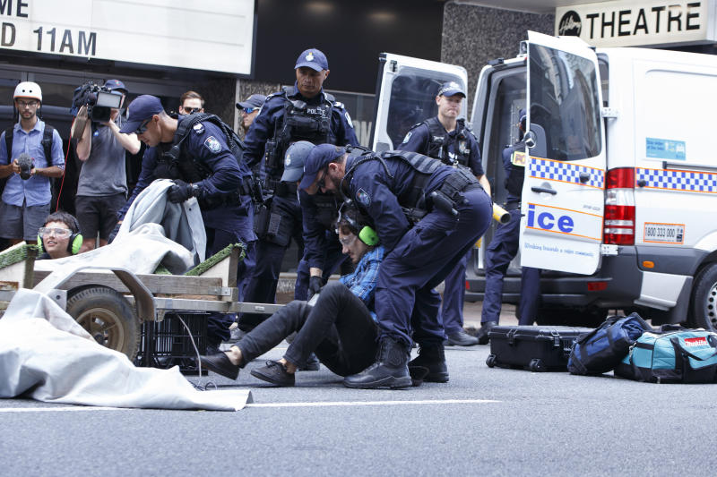 An Extinction Rebellion protester is placed under arrest by Queensland Police after being cut from a metal structure used to block the flow of traffic on George Street on Tuesday. Source: Joshua Prieto / SOPA Images/Sipa USA.