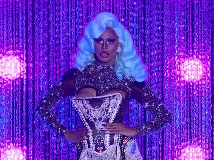 Shea Couleé in blue wig and black ensemble on drag race