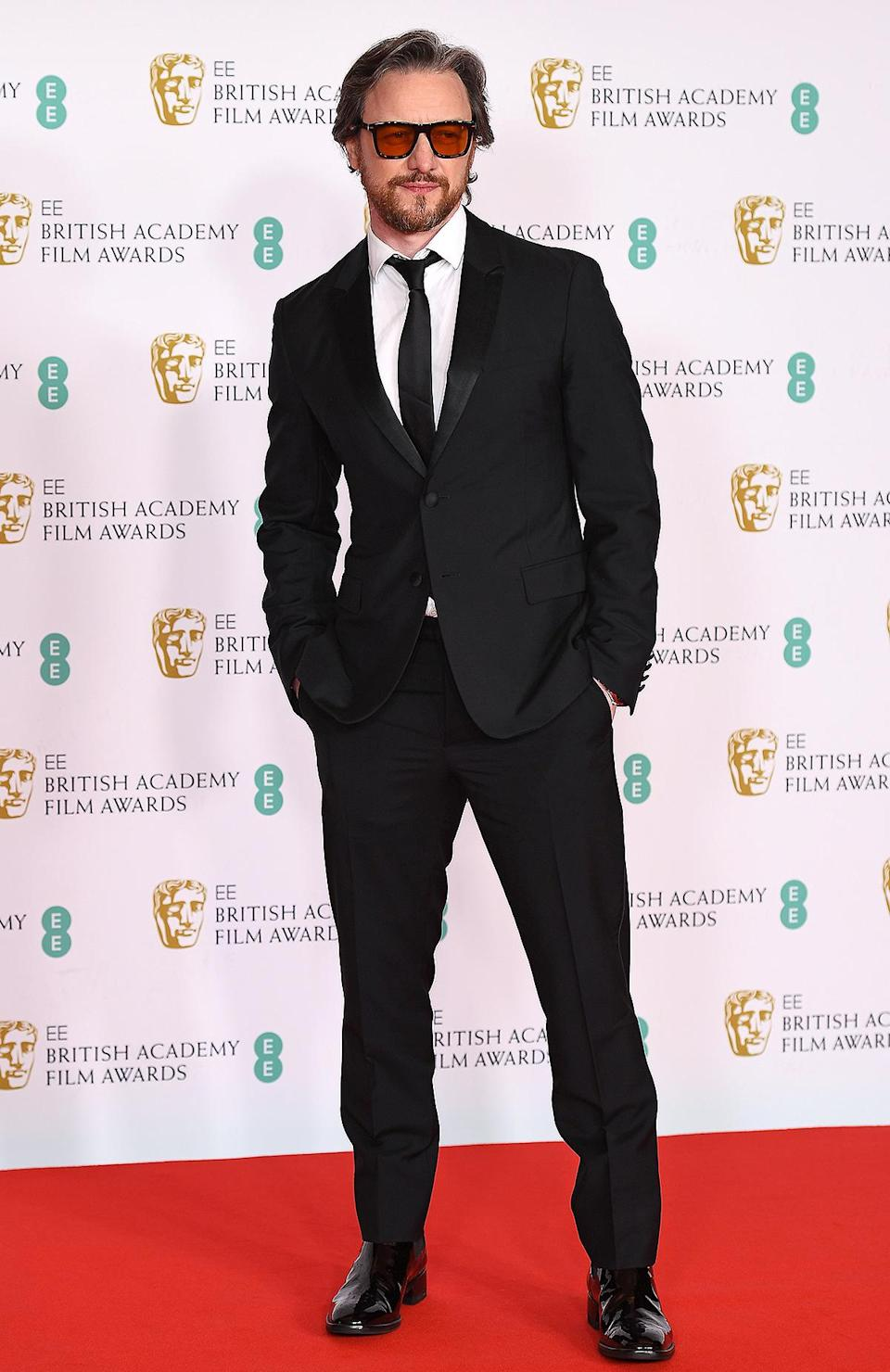 <p>pairs his classic black suit and tie with a pair of sunglasses from Eyewear by David Beckham. </p>