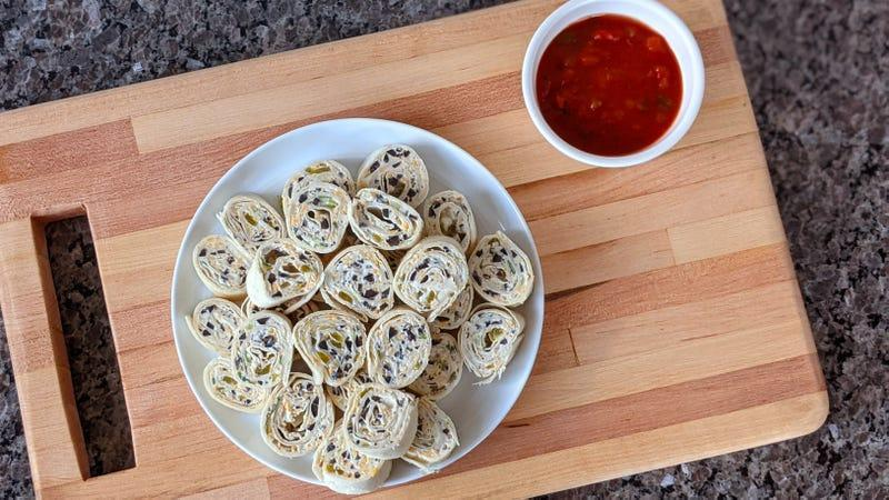 Plate of Cheesy Tortilla Roll-Ups beside bowl of red salsa on wooden cutting board