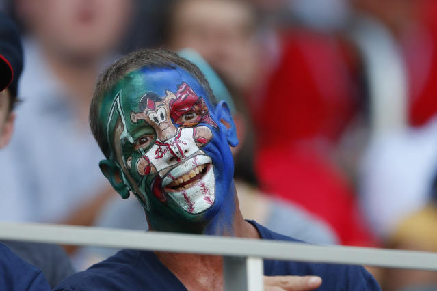 A fan has Atlanta Braves mascot Blooper's likeness painted on his face before a baseball game between the New York Mets and the Atlanta Braves Tuesday, Aug. 13, 2019, in Atlanta. (AP Photo/John Bazemore)