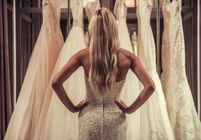 Back view of attractive young bride choosing wedding dress in modern wedding salon