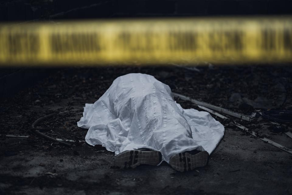 The dead body is seen lying on the ground behind a cordon tape.