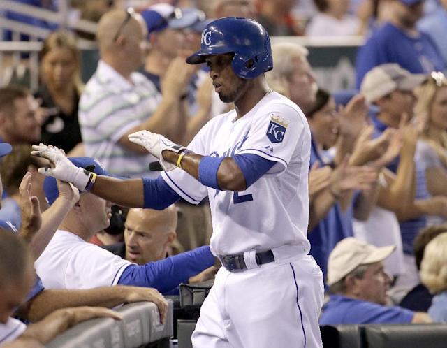 Kansas City Royals' Alcides Escobar celebrates after scoring on a double by Norichika Aoki during the third inning of a baseball game against the Texas Rangers, Tuesday, Sept. 2, 2014, in Kansas City, Mo. (AP Photo/Charlie Riedel)