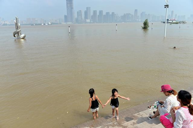 <p>People spend time at a flooded bank of the Yangtze River in Wuhan, Hubei province, China, July 3, 2017. (Photo: Stringer/Reuters) </p>