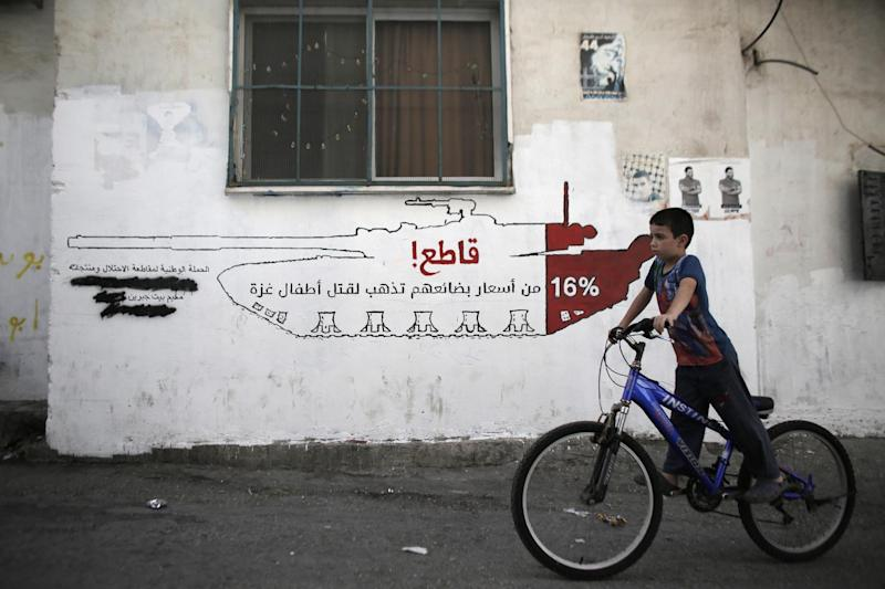 """A Palestinian boy rides his bicycle past graffiti reading: """" Boycott! 16% of the cost of their (Israeli) products goes into the killing of children in Gaza"""", in the al-Azzeh refugee camp on September 17, 2014 (AFP Photo/Ahmad Gharabli)"""