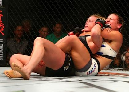 Miesha Tate applies a chokehold to win by submission against Holly Holm at UFC 196. (Reuters)