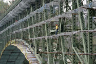 A worker stands on scaffolding attached to the Deception Pass Bridge, a 976-foot span about 180-feet above the waters below, as work to replace corroded steel and paint the structure continues Thursday, April 29, 2021, in Deception Pass, Wash. The 86-year old bridge, along with its 511-foot long companion Canoe Pass Bridge, spanning immediately to the north, connect Whidbey Island on the south to Fidalgo Island. Raising state taxes to improve roads and bridges is one of the few things many Republican and Democratic lawmakers have agreed on in recent years. Those efforts have slowed to a crawl this year, even as lawmakers acknowledge a widening gap between needed work and the money to pay for it. (AP Photo/Elaine Thompson)