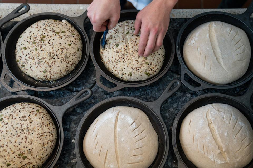 Jyan Isaac Horwitz scores sourdough bread that's ready to go into the oven.