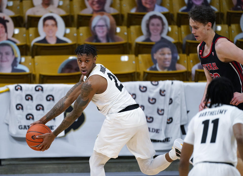 Colorado guard Eli Parquet, back left, pulls in a loose ball as Utah forward Mikael Jantunen, back right, and Colorado guard Keeshawn Barthelemy look on in the second half of an NCAA college basketball game Saturday, Jan. 30, 2021, in Boulder, Colo. Utah won 77-74. (AP Photo/David Zalubowski)