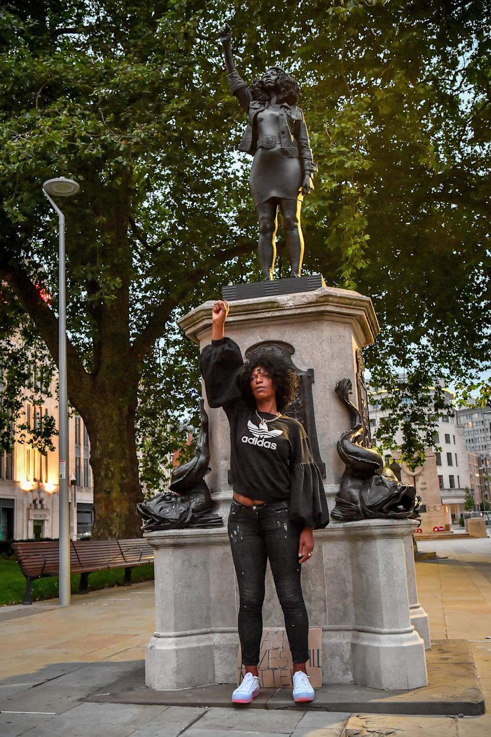 Jen Reid poses in front of her black resin and steel statue titled A Surge of Power (Jen Reid) 2020, by Marc Quinn, where it is installed on the vacant Edward Colston plinth in Bristol city centre. (Photo: PA)