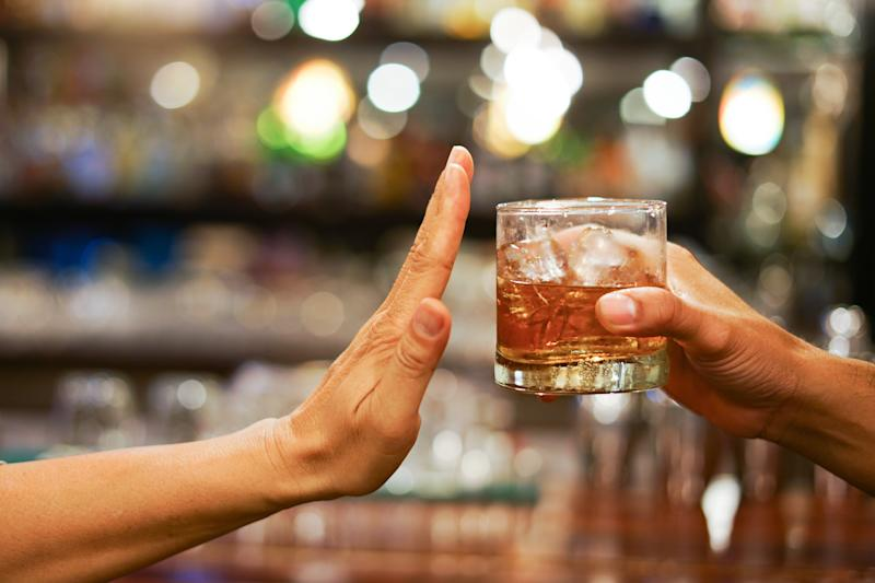 Stop drinking,Stop drinking conceptMan alcoholic social problems sitting at table refusal of alcohol say no to addiction close-up