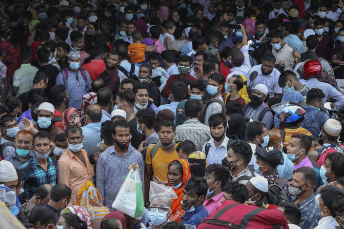 Thousands of people leaving for their native places to celebrate Eid-al-Fitr throng the Mawa ferry terminal ignoring risks of coronavirus infection in Munshiganj, Bangladesh, Thursday, May 13, 2021. (AP Photo/Mahmud Hossain Opu)