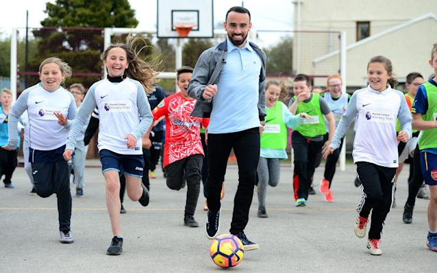 <span>Leon Britton is chased by school children at Pontybrenin Primary School</span> <span>Credit: Getty Images </span>