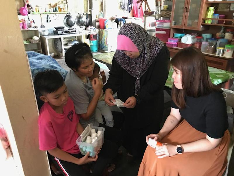 Wong (right) and Zarina looking through the pile of medication that 12-year-old nose cancer patient Cyle Addel takes. — Picture courtesy of The Malaysian AIDS Foundation