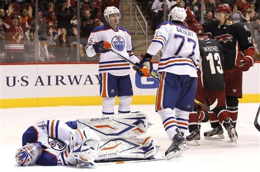 Edmonton Oilers' Devan Dubnyk (40) remains on the ice after giving up at Phoenix Coyotes goal as Coyotes' Ray Whitney (13) and Martin Hanzal (11), of the Czech Republic, celebrate and Oilers' Ladislav Smid (5), of the Czech Republic, and Tom Gilbert (77) look at one another in the second period in an NHL hockey game Thursday, Dec. 15, 2011, in Glendale, Ariz.(AP Photo/Ross D. Franklin)