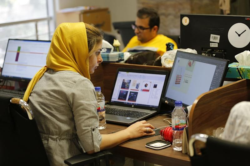 This file picture taken on July 09, 2017 shows employees at an e-commerce site's offices in the Iranian capital Tehran (AFP Photo/ATTA KENARE)