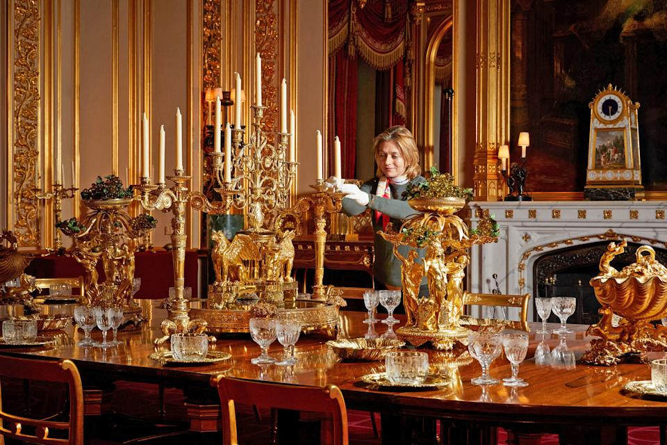 <p>A Royal Collection Trust curator puts the finishing touches on a special display of the silver-gilt Grand Service in the State Dining Room at Windsor Castle</p>PA