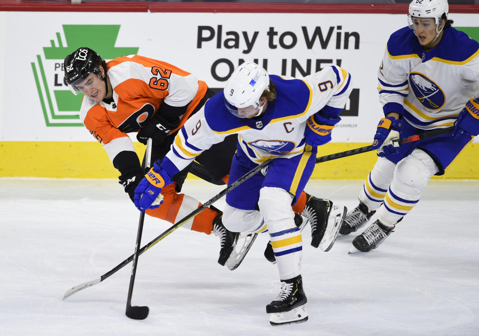 Philadelphia Flyers' Nicolas Aube-Kubel (62) is upended by Buffalo Sabres' Jack Eichel (9) during the first period of an NHL hockey game, Monday, Jan. 18, 2021, in Philadelphia. (AP Photo/Derik Hamilton)