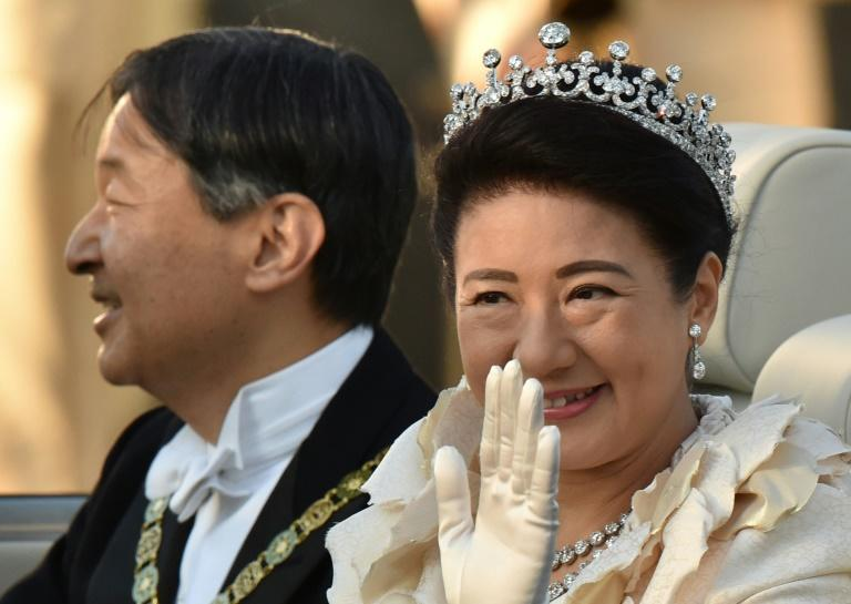 Japan's Emperor Naruhito and Empress Masako wave during their royal parade in Tokyo