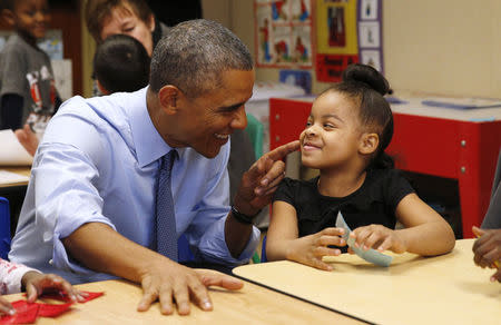 U.S. President Barack Obama touches the cheek of Akira Cooper during a visit to the Community Children's Center in Lawrence