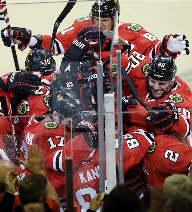Chicago Blackhawks' Patrick Kane (88) celebrates with teammates after scoring the game-winning goal during overtime period in Game 4 of a first-round NHL hockey playoff series against the St. Louis Blues in Chicago, Wednesday, April 23, 2014. The Blackhawks won 4-3 in overtime. (AP Photo/Nam Y. Huh)