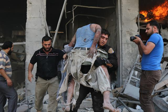 A member of the Syrian Civil Defense, also known as White Helmets, carries a victim followingthe airstrike at theMaaret al-Numan market.