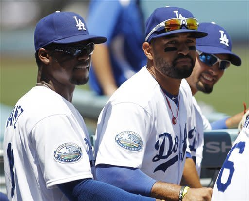 Los Angeles Dodgers shortstop Hanley Ramirez, left, center fielder Matt Kemp, center, and left fielder Shane Victorino, right, wait in the dugout to take the field before the baseball game against the Chicago Cubs on Sunday, Aug. 5, 2012, in Los Angeles. (AP Photo/Danny Moloshok)