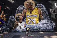 FILE - In this Jan. 26, 2021, file photo, Adam Dergazarian, bottom center, pays his respects for Kobe Bryant and his daughter, Gianna, in front of a mural painted by artist Louie Sloe Palsino in Los Angeles. Federal safety officials are expected to vote Tuesday, Feb. 9, 2021, on what likely caused the helicopter carrying Kobe Bryant, his 13-year-old daughter and seven others to crash into a Southern California hillside last year, killing all aboard. (AP Photo/Jae C. Hong, File)