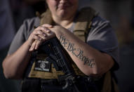 """The tattoo """"We The People"""", a phrase from the United States Constitution, decorates the arm of Trump supporter Michelle Gregoire as she rests her hand on her gun during a protest over the election results outside the central counting board at the TFC Center in Detroit, Friday, Nov. 6, 2020. (AP Photo/David Goldman)"""