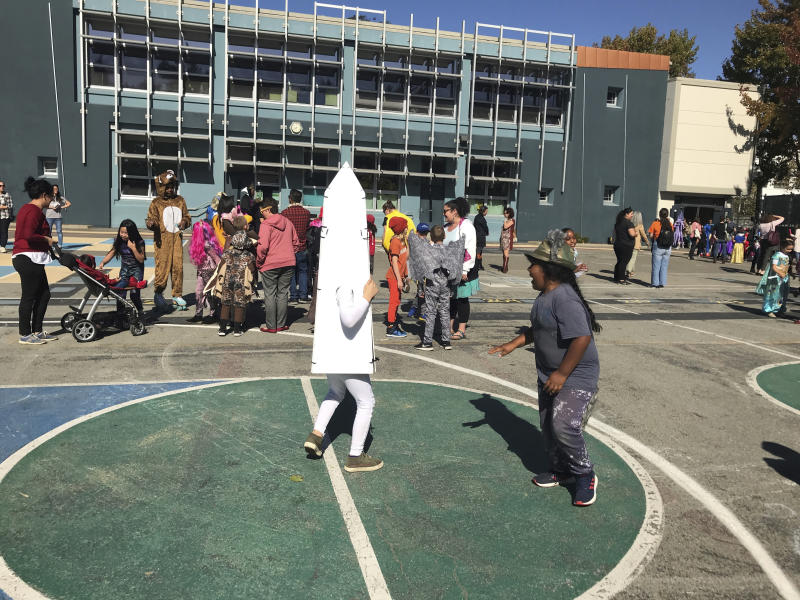 Children at Washington Elementary in Berkeley, Calif., play during the school's annual Halloween costume parade outside on Thursday, Oct. 31, 2019. The school had considered holding the parade indoors if the air quality was questionable because of a massive wildfire in Northern California's wine country. For tens of thousands of children in California, the biggest monsters this Halloween are wildfires that have thrown trick-or-treating into disarray. (AP Photo/Liz Schultz)