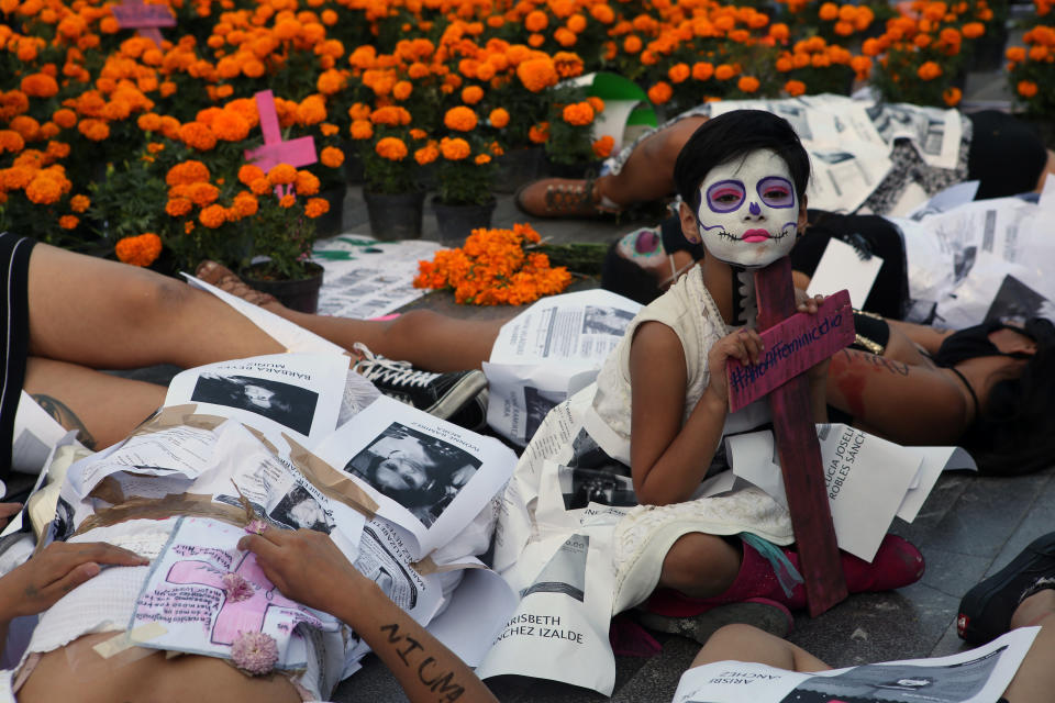 "A girl is surrounded by women dressed as ""Catrinas"" during a performance to demand justice for victims of femicide on Day of the Dead in Mexico City, Sunday, Nov. 1, 2020. (AP Photo/Ginnette Riquelme)"