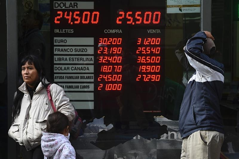 Currency exchange values are seen in the buy-sell board of a foreign exchange bureau in downtown Buenos Aires on May 15