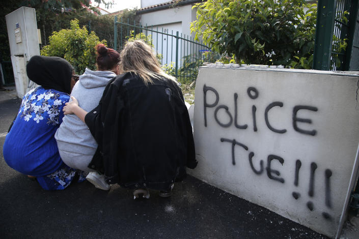 FILE - In this July 5, 2018 file photo, girls lay flowers at the site where police shot of a driver apparently trying to avoid an identity check earlier that week, and where a graffiti read Police Kills, in Nantes, western France. As videos helped reveal many cases of police brutality, French civil rights activists voiced fears that a new security law would threaten efforts by people from minorities and poor neighborhoods to document incidents involving law enforcement officers. French President Emmanuel Macron's government is pushing a new security bill that would notably make it illegal to publish images of officers with intent to cause them harm (AP Photo/Michel Euler, File)