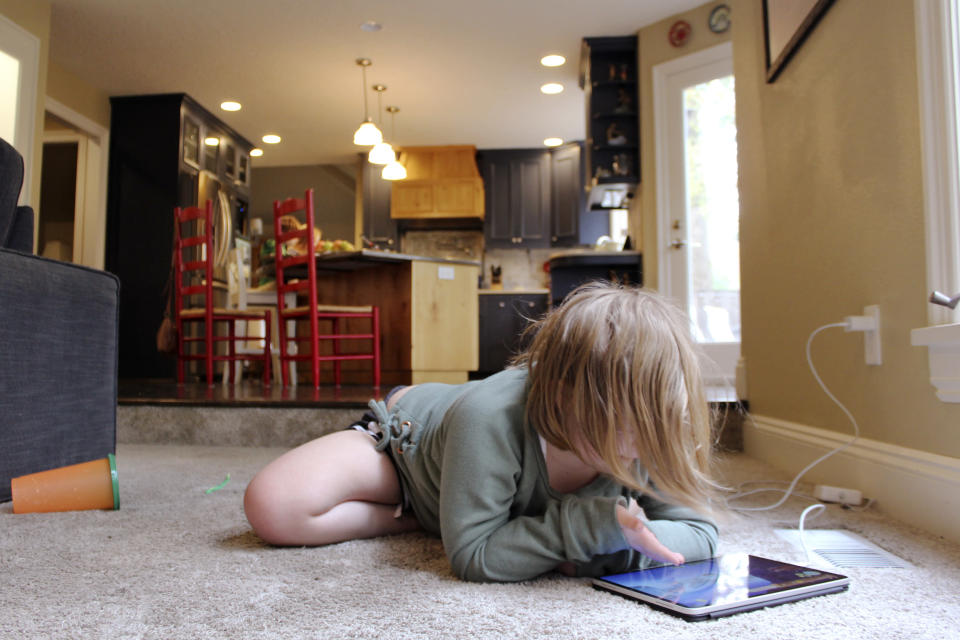 Lizzie Dale sprawls on the floor to play games on an iPad as her siblings work on school work in the kitchen behind her in their home in Lake Oswego, Ore., Oct. 30, 2020. In Oregon, one of only a handful of states that has required a partial or statewide closure of schools in the midst of the COVID-19 pandemic, parents in favor of their children returning to in-person learning have voiced their concerns and grievances using social media, petitions, letters to state officials, emotional testimonies at virtual school board meetings and on the steps of the state's Capitol. (AP Photo/Sara Cline)