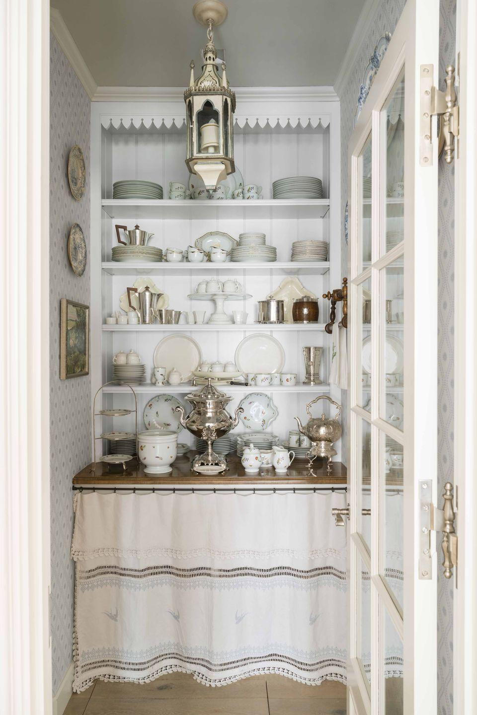 """<p>In this <a href=""""https://www.veranda.com/decorating-ideas/a9978895/dallas-spanish-colonial/"""" rel=""""nofollow noopener"""" target=""""_blank"""" data-ylk=""""slk:historic Dallas home"""" class=""""link rapid-noclick-resp"""">historic Dallas home</a>, designer <a href=""""http://www.cathy-kincaid.com/"""" rel=""""nofollow noopener"""" target=""""_blank"""" data-ylk=""""slk:Cathy Kincaid"""" class=""""link rapid-noclick-resp"""">Cathy Kincaid</a> converted a small closet into a butler's pantry which doubles as both a china and silver display as well as a beverage serving station. A textile hung below the wooden counter conceals additional storage. The wallpaper is by <a href=""""https://www.stylelibrary.com/zoffany/"""" rel=""""nofollow noopener"""" target=""""_blank"""" data-ylk=""""slk:Zoffany"""" class=""""link rapid-noclick-resp"""">Zoffany</a>. </p><p><a class=""""link rapid-noclick-resp"""" href=""""https://go.redirectingat.com?id=74968X1596630&url=https%3A%2F%2Fwww.etsy.com%2Flisting%2F659834829%2Fsilver-plated-coffee-pot-sheridan%3Fga_order%3Dmost_relevant%26ga_search_type%3Dall%26ga_view_type%3Dgallery%26ga_search_query%3Dsilver%2Bcoffee%2Bpot%26ref%3Dsr_gallery-1-4%26cns%3D1&sref=https%3A%2F%2Fwww.veranda.com%2Fdecorating-ideas%2Fg28837805%2Fhome-bar-ideas%2F"""" rel=""""nofollow noopener"""" target=""""_blank"""" data-ylk=""""slk:Find Similar Vintage Servingware Here"""">Find Similar Vintage Servingware Here</a></p>"""
