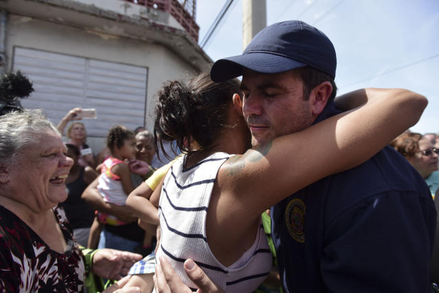 A San Juan resident hugs Gov. Ricardo Rosselló as the National Guard arrives at Barrio Obrero in Santurce to distribute water and food to those affected by Hurricane Maria in September 2017. (Photo: Carlos Giusti/AP)