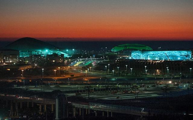 FOR USE AS DESIRED WITH SOCHI 2014 OLYMPICS STORIES - FILE - In this Thursday, Oct. 24, 2013, file photo, the Bolshoi Ice Dome, background center, Iceberg skating arena, right, and the Fisht Olympic Stadium, left, are illuminated at night in Sochi, Russia. Sochi will host the 2014 Winter Olympic Games next month. (AP Photo/Lesya Polyakova, File)