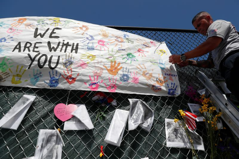 A member of the Miami-Dade Fire Rescue unit places a sign on a makeshift memorial for the victims of the Surfside's Champlain Towers South condominium collapse in Miami, Florida