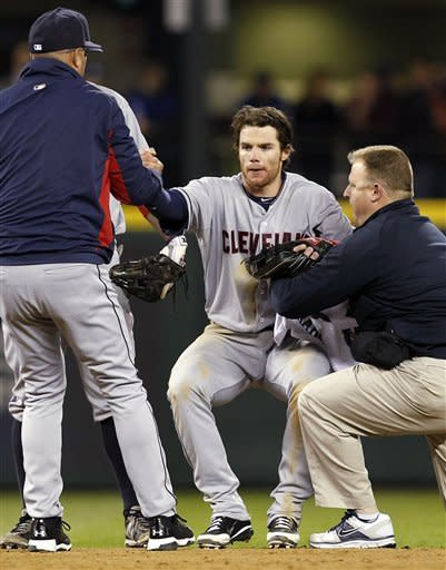 Cleveland Indians shortstop Jason Donald is helped to his feet after being injured in the ninth inning of a baseball game against the Seattle Mariners Tuesday, April 17, 2012, in Seattle. Donald remained in the game. Cleveland won 9-8. (AP Photo/Elaine Thompson)