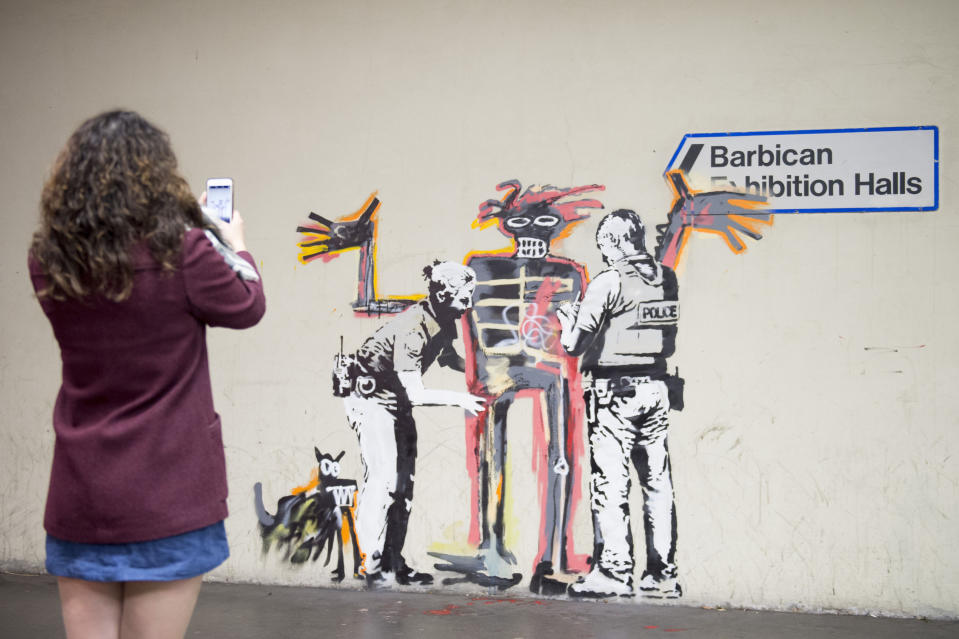 A woman takes a photo of one of two new murals painted by the artist Banksy near the Barbican Centre in London. The works mark the opening of an exhibition by American artist Jean-Michel Basquiat at the arts venue.