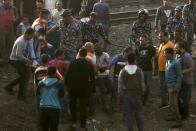 Medics carry an injured man at the site where a passenger train derailed injuring at least 100 people, in Banha, Qalyubia province, Egypt, Sunday, April 18, 2021. At least eight train wagons ran off the railway, the provincial governor's office said in a statement. (AP Photo/Fadel Dawood)