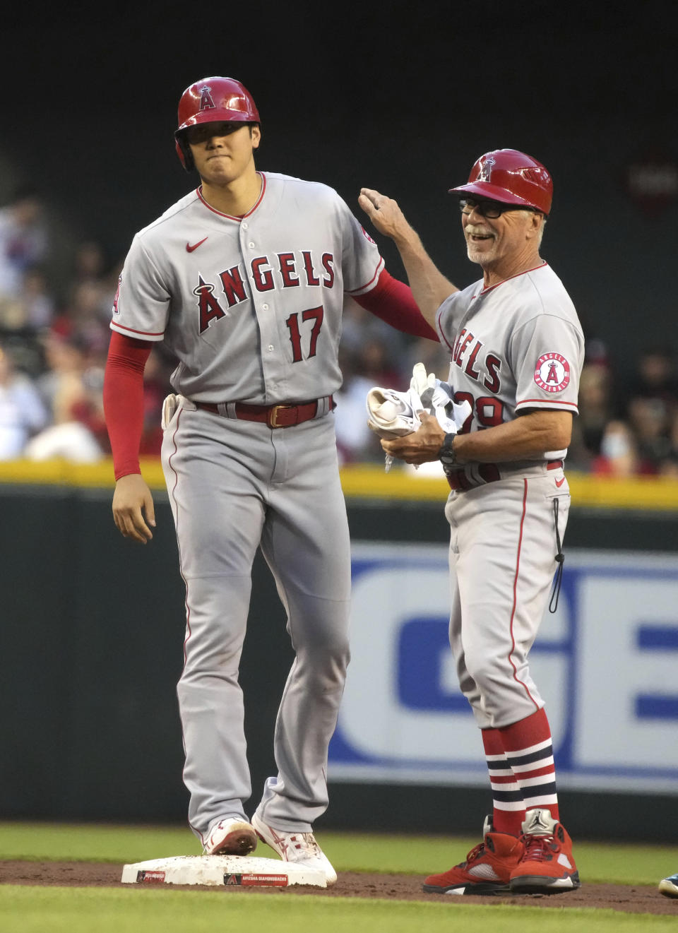 Los Angeles Angels' Shohei Ohtani (17) laughs with first base coach Bruce Hines after hitting an RBI-double against the Arizona Diamondbacks in the third inning during a baseball game, Friday, June 11, 2021, in Phoenix. (AP Photo/Rick Scuteri)