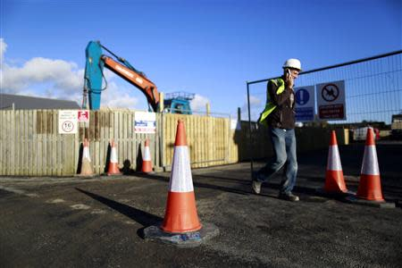 A construction worker makes a call on his phone at 'The Cedars' housing development site in the town of Swords situated on the outskirts of Dublin November 4, 2013. The government is counting on places like Swords to resuscitate construction and spur consumer spending on houses and the high street, thereby smoothing Ireland's escape from a 85 billion euro ($117 billion) bailout. Ireland's economy has to expand by an annual 2-3 percent to make its debt sustainable and the government's strategy to achieve this - placing construction at its heart - started to emerge in October with its finance minister's 2014 budget. REUTERS/Cathal McNaughton