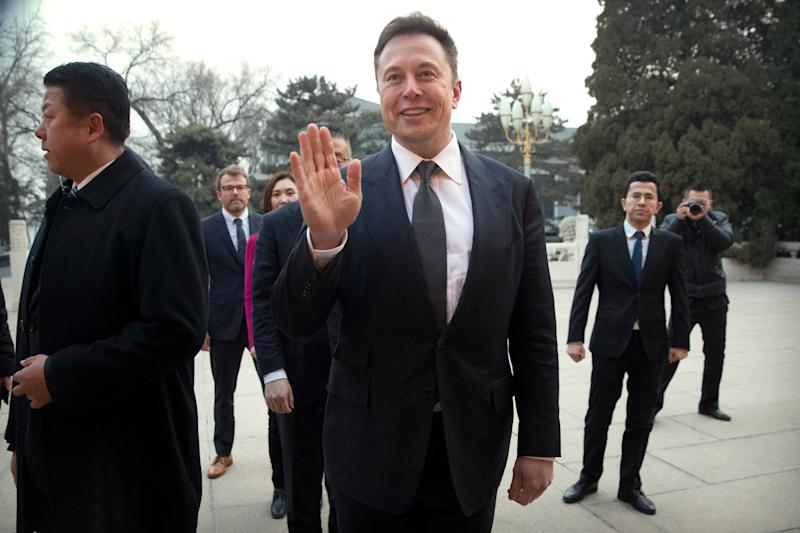 Tesla CEO Elon Musk, center, waves as he waits for a meeting with Chinese Premier Li Keqiang at the Zhongnanhai leadership compound in Beijing, Wednesday, Jan. 9, 2019. (AP Photo/Mark Schiefelbein, Pool)