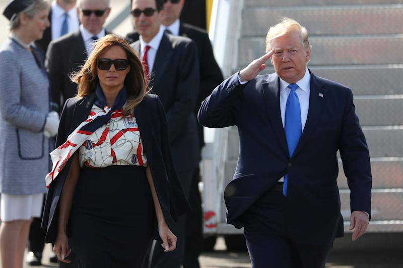 US President Donald Trump (R) salutes the honour guard as he and US First Lady Melania Trump (L) walk on the tarmac after disembarking Air Force One at Stansted Airport, north of London on June 3, 2018, as they begin a three-day State Visit to the UK. - Britain rolled out the red carpet for US President Donald Trump on June 3 as he arrived in Britain for a state visit already overshadowed by his outspoken remarks on Brexit. (Photo by Isabel Infantes / AFP) (Photo credit should read ISABEL INFANTES/AFP/Getty Images)