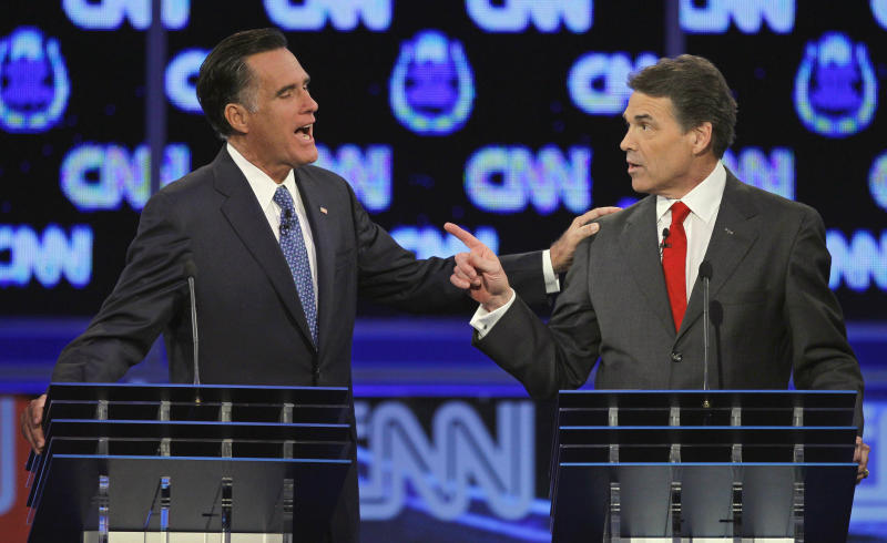 FILE - In this Oct. 18, 2011 file photo, Republican presidential candidates, former Massachusetts Gov. Mitt Romney, left, and Texas Gov. Rick Perry, speak during a Republican presidential debate in Las Vegas. The image of Romney laying a hand on Perry's shoulder may well be remembered long after people have forgotten that the two were squabbling about. Body language speaks volumes in political debates.  (AP Photo/Chris Carlson, File)