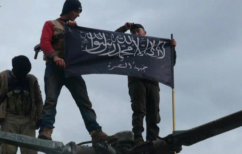 """This citizen journalism image provided by Edlib News Network, ENN, which has been authenticated based on its contents and other AP reporting, shows rebels from al-Qaida affiliated Jabhat al-Nusra, wave their brigade flag as they step on the top of a Syrian air force helicopter, at Taftanaz air base that was captured by the rebels, in Idlib province, northern Syria, Friday Jan. 11, 2013. Islamic militants seeking to topple President Bashar Assad took full control of a strategic northwestern air base Friday in a significant blow to government forces, seizing helicopters, tanks and multiple rocket launchers, activists said. The Arabic words on the flag read:""""There is no God only God and Mohamad his prophet, Jabhat al-Nusra (their brigade name)"""". (AP Photo/Edlib News Network ENN)"""
