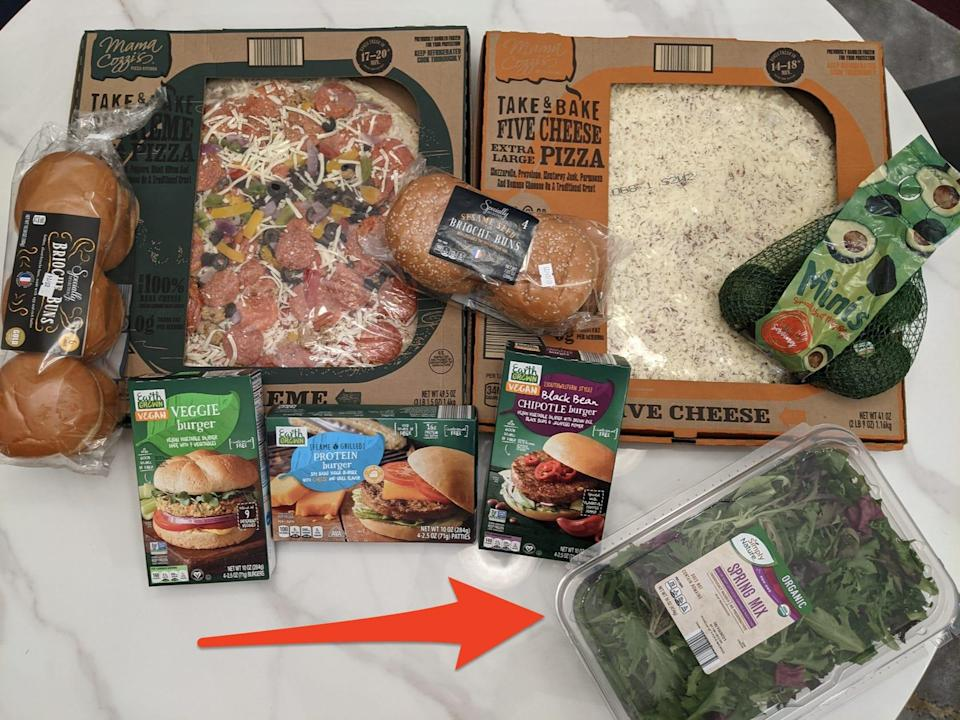 Pizza, broiche buns, avocafos, and veggies burgers all in an original packaging on a white table top as well as a red arrow pointing toward a plastic package of Aldi salad greens